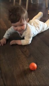 Baby playing with a ball on a hardwood floor.